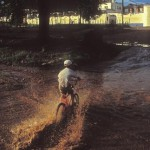 bike rider crossing flooded arroyo, Alamos, Sonora, Mexico. Photo by Anders Tomlinson.