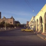 Man waiting in the plaza warmed by morning sun. Alamos, Sonora, Mexico. Photo by Anders Tomlinson.
