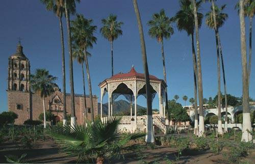 Sierra de Alamos, Bishop Reyes Cathedral, Plaza de Las Armas garden and kiosk and Hotel Los Portales.  Alamos, Sonora, Mexico.  Photo by Anders Tomlinson.