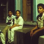 4 boys on sidewalk with cat at night, Alamos, Sonora, Mexico. Photo by Anders Tomlinson.