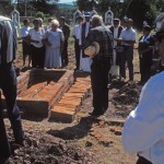 Bricks are placed on top of the beam lowered onto the casket, Alamos, Sonora, Mexico. Photo by Anders Tomlinson.