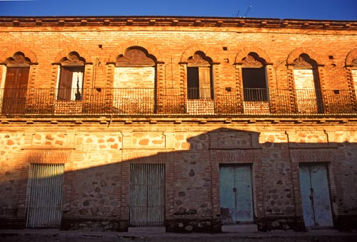 Sunrise shadoes on the red brick building, Calle Gral Antonio Rosales and Calle Mariano Matamoro, Alamos, Sonora, Mexico.  Photo by Anders Tomlinson.