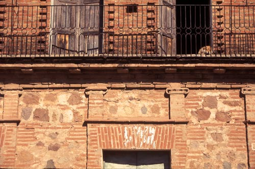 Detail with sleeping pup, red-brick building on Calle Gral Antonio Rosales and Calle Mariano Matamoros, Alamos, Sonora, Mexico.  Photo by Anders Tomlinson.