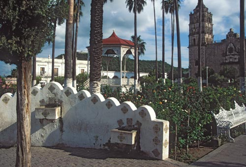 Plaza de las Armas, bandstand-kiosk, Bishop Reyes' Cathedral. Old Alamos Hotel, and the Mirador.  Alamos. Sonora, Mexico.  Photo by Anders Tomlinson.