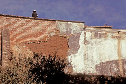 A guard stands guard on the high walls in need of repair.  Alamos, Sonora, Mexico.  Photo by Anders Tomlinson.